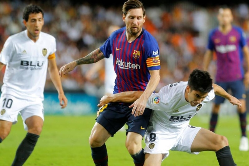Holders Barcelona were held to a 1-1 draw by Valencia while Atletico Madrid and Sevilla registered victories over Real Betis and Celta Vigo on Sunday.
